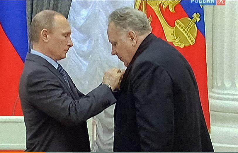 Vladimir Putin is fastening a badge on Vladislav Krapivin's breast