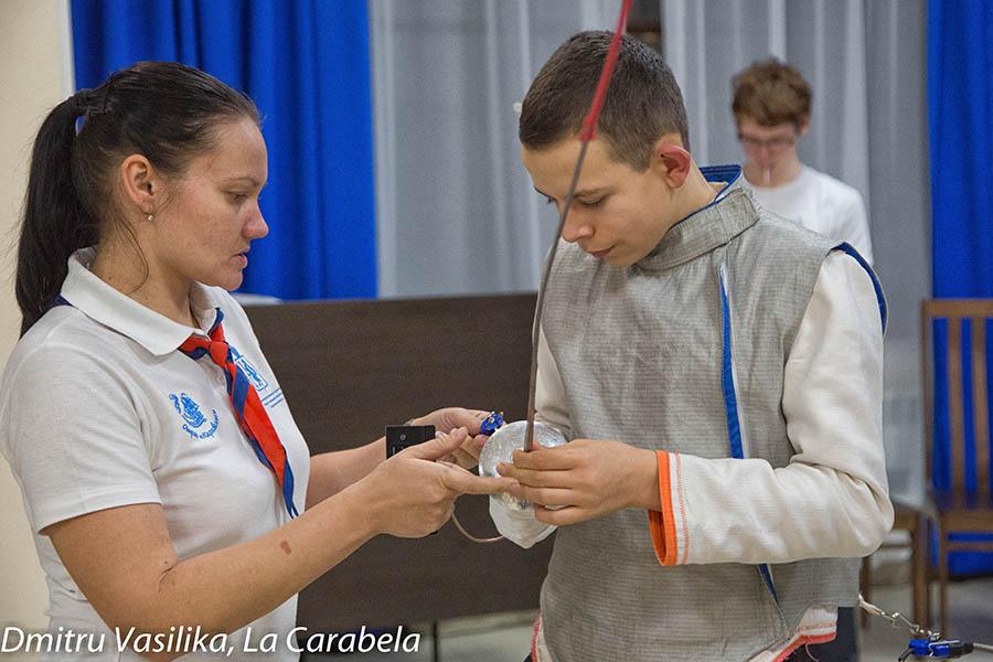 Старший судья Мария Доможирова помогает бойцу подключить рапиру