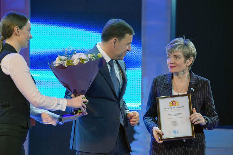 Евгений Куйвашев вручает почётный диплом для общественной детской организации «Каравелла» её командору Ларисе Крапивиной
