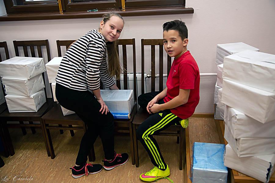 Данияр и Лиза заматывают книги в плёнку, чтобы не отсырели в подвале